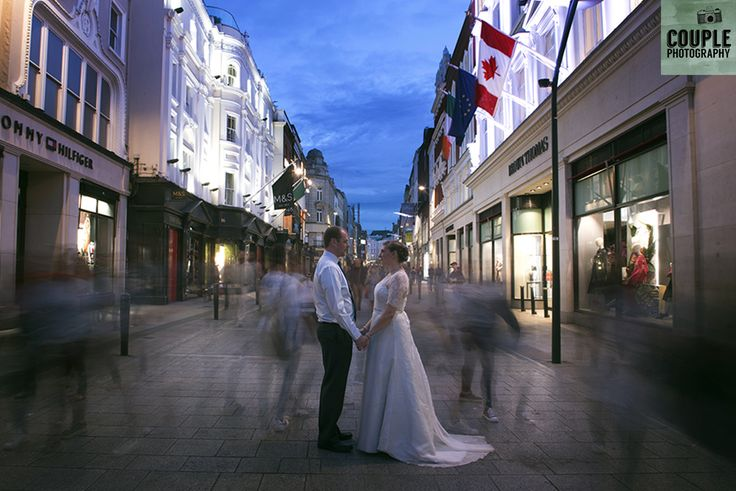 standing on Grafton Street at night with the world going by. Real Wedding by Couple Photography