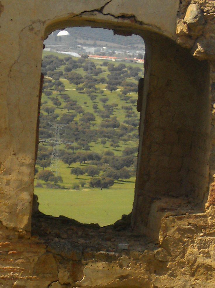 Vistas de la dehesa extremeña a través de una ventana en las ruinas del castillo de Belvís de Monroy.