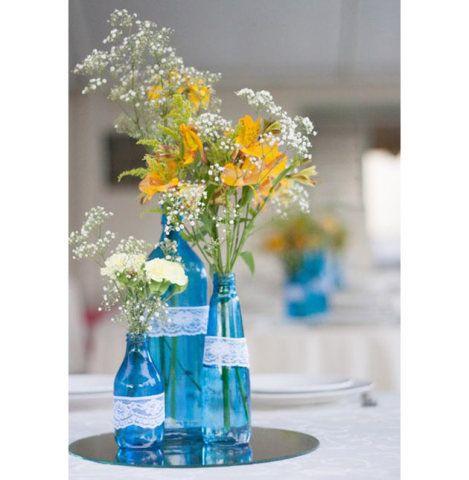 Não são apenas garrafas de vidro que podem ser significados e ganhar outros papéis na decoração. Essas garrafas de plástico, por exemplo, foram utilizadas para decorar mesas em um casamento. Uma ótima dica para compor mesas em eventos para receber convidados.
