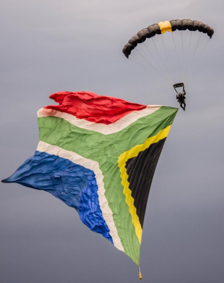 Skydiver with a huge South African flag suspended below him. BelAfrique your personal travel planner - www.BelAfrique.com