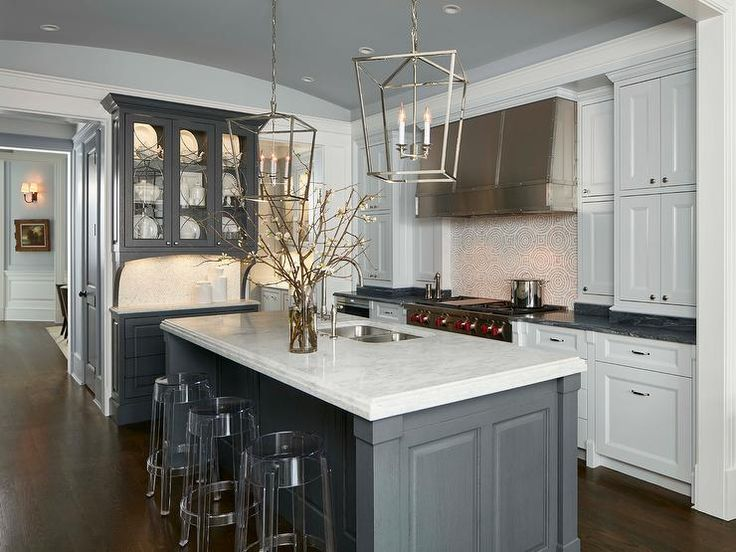 Stunning kitchen features white shaker cabinets paired with black marble countertops and a mosaic tiled backsplash.