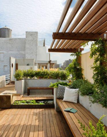 bankje hout met witte muur met daarin planten en overhangende overkapping
