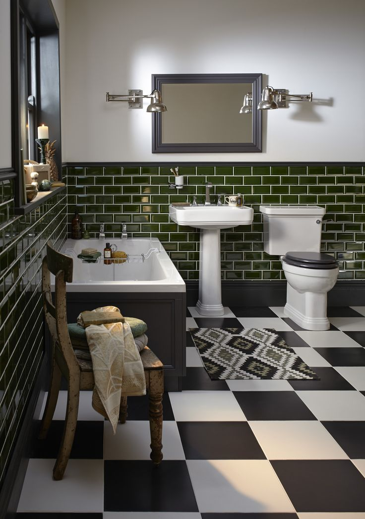 Heritage Bathrooms Wynwood suite with fitted cast iron bath, bottle green wall tiles, Edgeware mirror in slate grey and graphic print mat