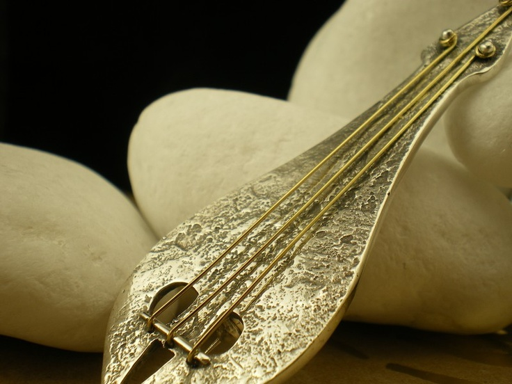 This lovely brooch is a representation of the musical instrument central to the traditional music of Crete, the three-stringed bowed Lyra. It is made from solid sterling silver while the strings are handcrafted from solid K18 gold. The brooch has an oxidized like surface (by reticulation) that beautifully contrasts the polished strings. http://eternal-elegance.com/index.php?page=shop.product_details&flypage=flypage.tpl&product_id=91&category_id=13&option=com_virtuemart&Itemid=215&lang=en