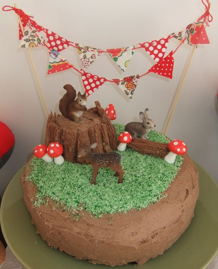 Woodland cake. Chocolate Flakes for bark/logs, green coconut for grass.