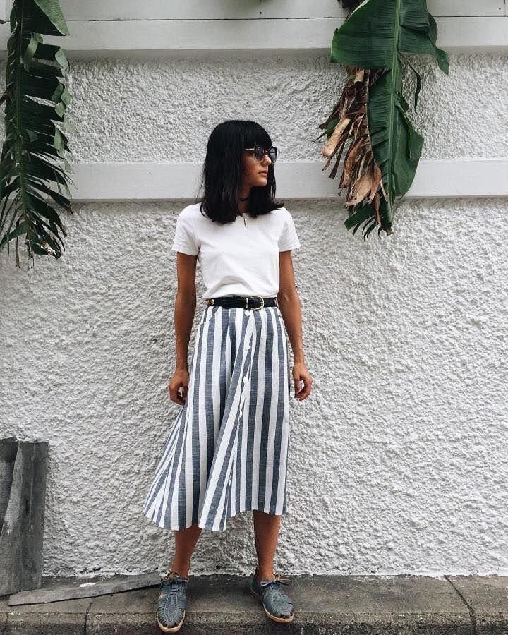 Tenue mi-saison pour le printemps : tee-shirt blanc, jupe mi-longue rayures bleu et blanc boutonnée sur toute la longueur, mocassins lacets bleus
