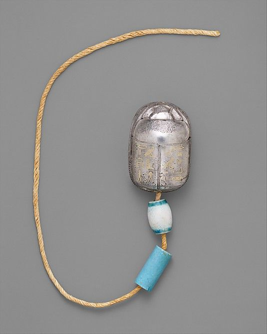 Scarab Bracelet of Wah Middle Kingdom Dynasty 12  reign of Amenemhat I, early ca. 1981–1975 B.C. From Egypt, Upper Egypt; Thebes, Southern Asasif, Tomb of Wah (MMA 1107), Mummy, over crossed wrists, MMA 1920 Medium: Silver, gold, glazed steatite, linen cord scarab: l. 3.9 cm (1 1/2 in); w. 2.7 cm (1 1/16 in); h. 2.5 cm (1 in) barrel bead: l. 1.4 cm (9/16 in); diam. 1 cm (3/8 in) cylindrical bead: l. 1.9 cm (3/4 in); 0.8 cm (5/16 in) overall length: 43 cm (16 15/16 in)