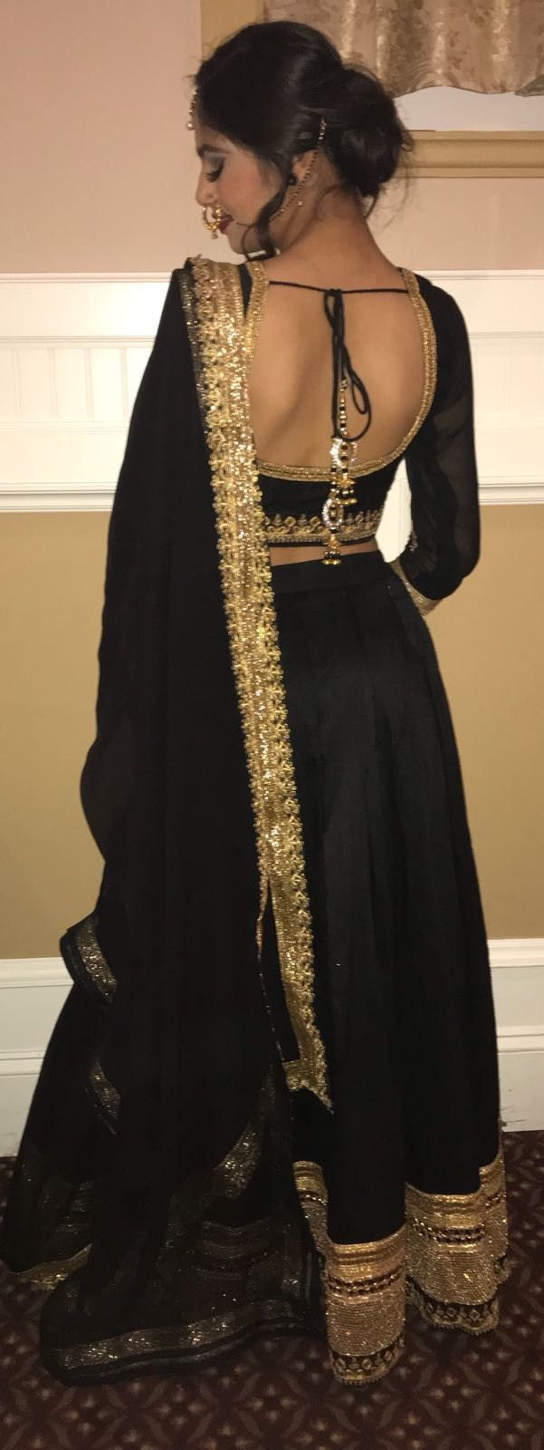 Lovely black and gold chiffon silk lehenga with heavy border and backless blouse with dori