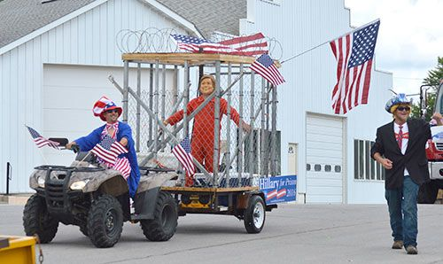 Kyle Julin, of Manilla, pulls a float with Adam Corky, of Odebolt, inside a cage dressed in a prison jumpsuit and Hillary Clinton mask on Saturday in Arcadia. Josh Reetz walks alongside, handing out water ballons for parade-goers to throw at the fake Clinton.