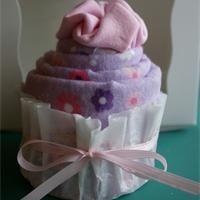 Idée pour un baby shower : les cup-cakes de bodys  Voici une idée originale qui pourra également être reprise pour faire un cadeau de naissance original : les cup-cakes de bodys. Le principe consiste à enrouler des bodys dans des couvertures de bébé de manière à donner l'impression qu'il s'agit de délicieux gâteaux.