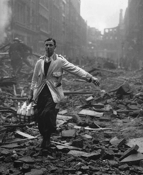 A milkman delivering on a London street devastated during a German bombing raid. 1940