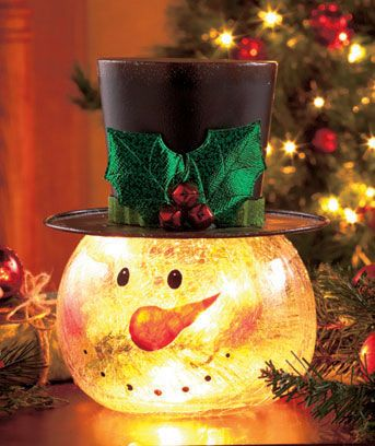 The jolly features of this Crackle Glass Snowman Light add a festive look to your decor. With handpainted facial details, the snowman's head lights up with a constant golden light. It's accented by a top hat with holly on the outside and faux pine sp