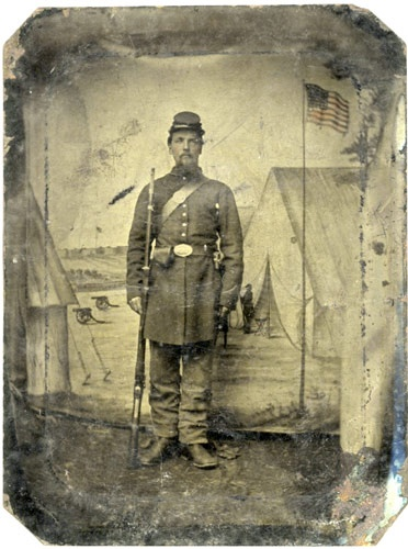 Tintype of Union Private posed in front of painted camp canvas backdrop.