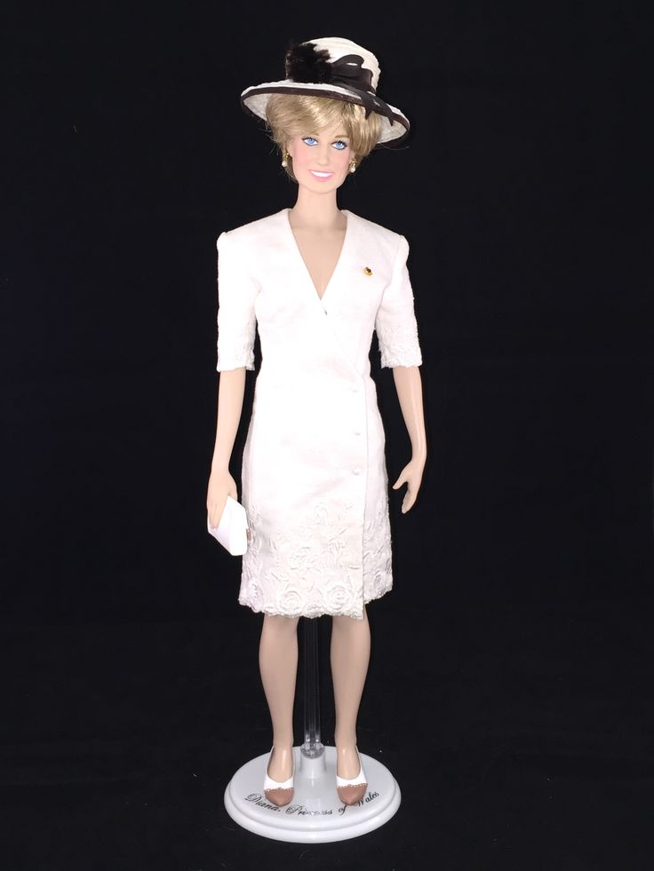 This Franklin Mint Diana doll is wearing a custom replica of a cream colored silk suit with satin embroidery & scalloped edges along with a two toned hat by designer Marina Killery. Princess Diana wore this suit to the Gulf Forces Parade in 1991.