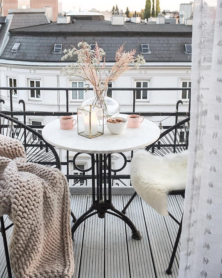 Photo of Beautiful white french inspired balcony with Acapulco chairs and cozy wool blank…