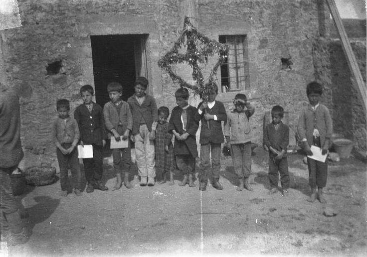 """Παιδάκια τραγουδούν τον Λάζαρο στην πλατεία της αγοράς, Αρχάνες, Τη θέση του """"Λάζαρου"""" έπαιρνε  στην Κρήτη ένας ξύλινος σταυρός που τον στόλιζαν με ορμαθούς από λεμονανθούς και αγριόχορτα με κόκκινα λουλούδια, τις μαχαιρίτσες.. Κρήτη  Φωτ.: John Linton Myres Aρχείο University of Oxford"""