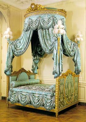 The traditional French canopied bed, lit à colonnes  (four-poster bed), ca. 1775-1780.  Painted and gilded walnut, modern upholstery with fringers,  cords, tassels and ostrich feathers