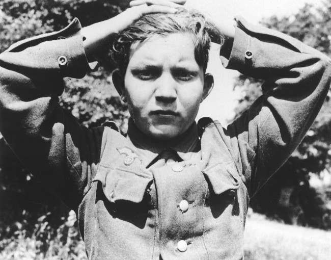 A 16-year old German soldier has his hands clasped over his head as he is taken prisoner with thousands of other Wehrmacht soldiers, at Cherbourg, France, during the Allied Normandy invasion in June 1944. (AP Photo)