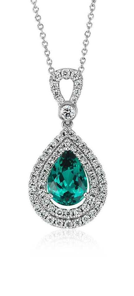 This one-of-a-kind striking pendant features a 1.95 carat vibrant pear shaped indicolite tourmaline framed by a halo of diamonds