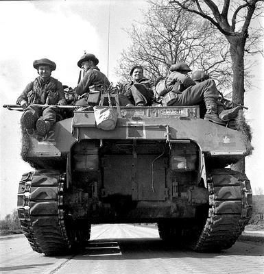 "Men of the 2nd Canadian Infantry Division hitch a ride on a Canadian ""Ram Kangaroo"" on the way to Groningen, Netherlands, April 1945."