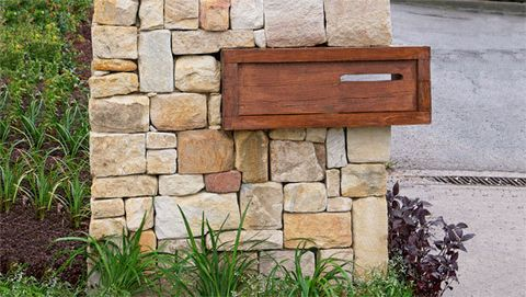 How to create a stone wall letterbox: Sandstone and hardwood can be visually stunning when used together, creating a natural and rustic yet sophisticated effect. If 'building in' a hardwood feature, as here, make sure your hardwood is well seasoned or kiln dried so it doesn't shrink and crack the stonework within a year or two.