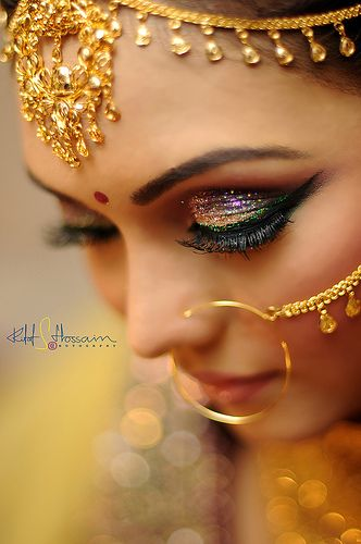 glittery gold, plum, and emerald eye makeup and full lashes!