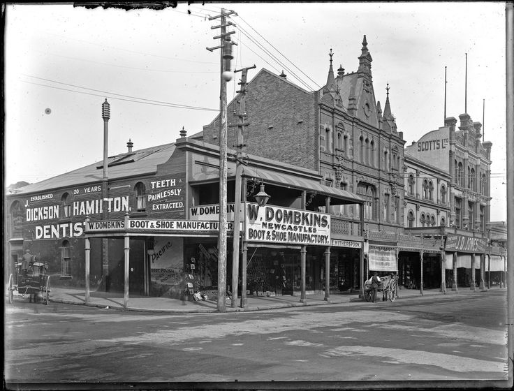 """This image was scanned from the original glass negative taken by Ralph Snowball. It is part of the Norm Barney Photographic Collection, held by Cultural Collections at the University of Newcastle, NSW, Australia.  Notes Image shows W. Dombkins boot and shoe store. Also seen in the image is Witherspoon's grocers, Green Bros jewellers, Charleston photographic studio and Scotts Ltd. (""""The Busy Drapers"""") . A store owned by J.D. Jones (""""The house for sterling value) can also be ..."""