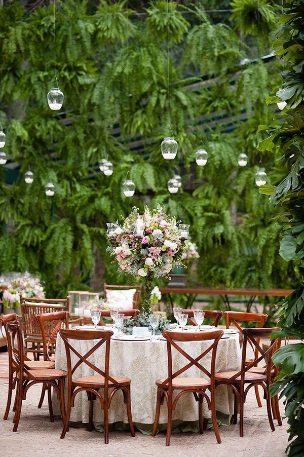Decoração de casamento na fazenda em tons suaves de rosa, lilás, bege e verde - mesa de convidados com arranjo central alto - muro verde de samambaias e velas pendentes ( Decoração: Fabio Borgatto e Telma Hayashi | Foto: Daniela Picoral )