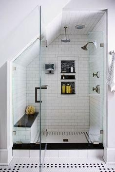 Gorgeous open walk in shower with white subway tiles, black trim and built-in shower bench and black and white patterned floor tiles.