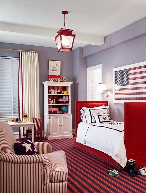 Ashley Whittaker Boy's Room with American Flag: Adorable Red Lantern, Framed Flag, Upholstered Red Canvas Bed, with Red/White Seersucker Armchair, White wooden bookcase, cabinetry, chambray blue walls