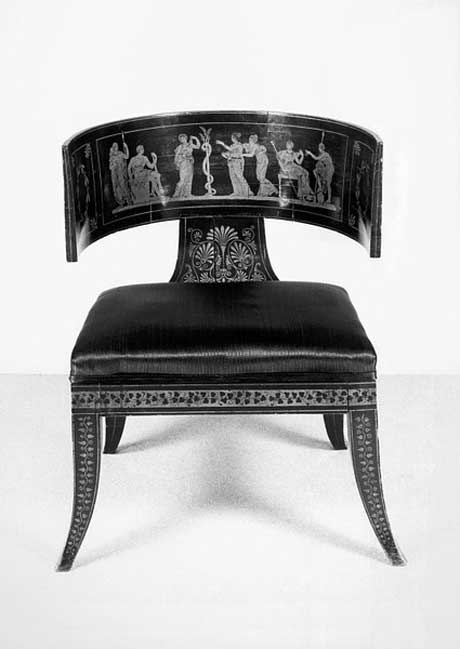 """The word klismos is of Greek origin as is the klismos chair, which is an ancient chair form that was extensively used by the Greeks. It was designed by an unknown designer in the 5th century. It was made for comfort, which can be seen in the way it reclines. If compared to a throne one could say, """" a throne is to rule from and a Klismos is to relax on"""". The shape may go even further back in history, and has made several re-appearances, most notably in English Regency and Empire styles."""