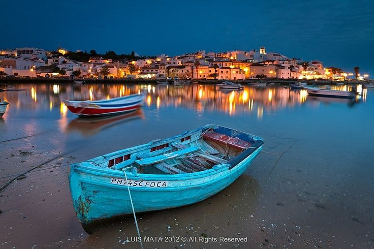 Ferragudo at dusk - Ferragudo is a small fisherman village near Portimão, in Algarve. At dusk the yellow and orange lights reflect in the Arade river, merging with the blue tones of the night.