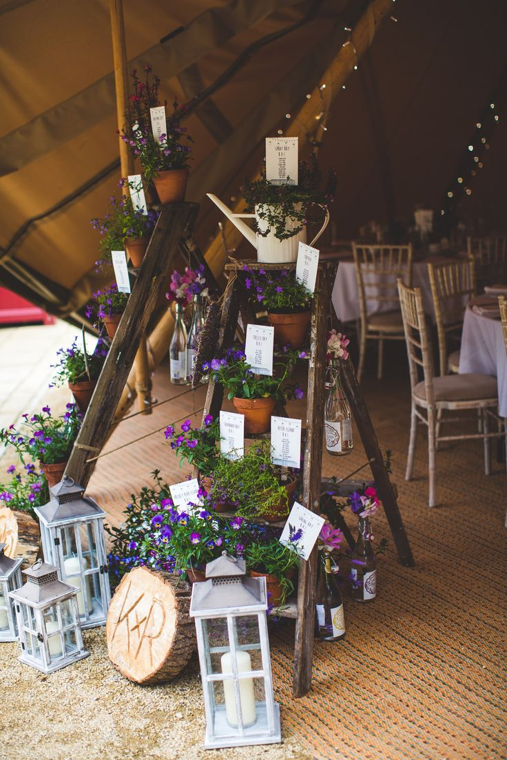Restored step ladder and planted flowers table plan with lanterns and slabs of wood -  Image by  S6 Photography - Cherish by Suzanne Neville and bridesmaid dresses by Maids To Measure for a rustic tipi wedding in Yorkshire with wild flowers.