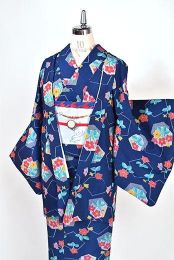 光がきらめくような幾何学模様に可憐なお花模様が重ねられたノスタルジックでキュートなデザインがシックなネイビーブルーをベースに織りだされたウールのアンサンブル(着物と羽織のセット)です。