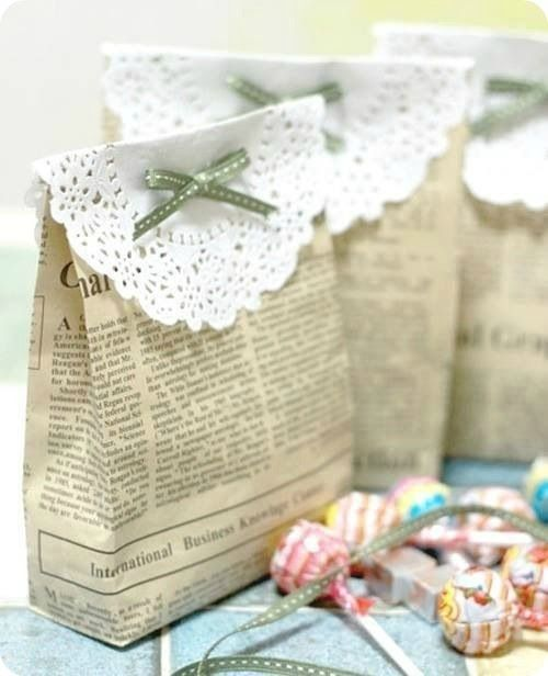 Newspaper gift bags topped with paper doilies and a bow