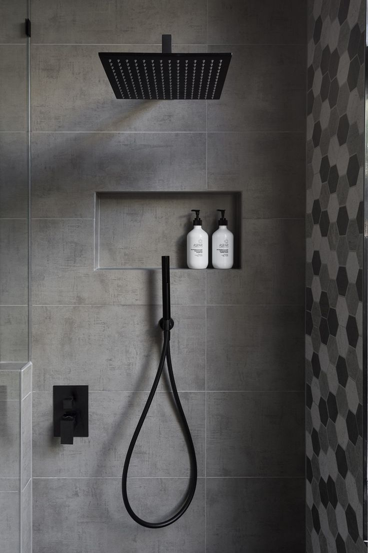 In this modern bathroom, the shower has a matte black rainfall shower head and a hand held shower head, as well as a tiled built-in shelf.