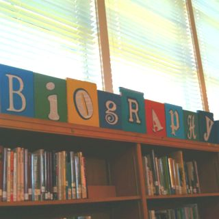 Sign for biography section of my library made with discarded books and book pages. I cut the letters from the pages and a dark blue. I glued these to the front of the books and then used Gorilla glue to glue the books to a 1x4. Last step was to screw two books onto the end to hold the sign up.