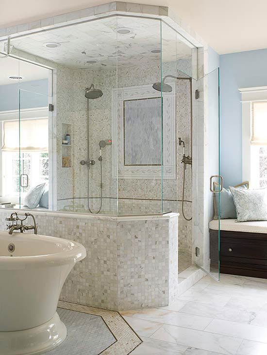 This luxurious frameless shower features two showerheads and various marble tiles. The custom mosaic mural on the shower wall acts as a framed piece of art. The shower also has two separate entrances, perfect for this spacious master bath.