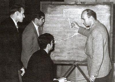 "The Soviet coach B.Uzakov explaining the tactics to his players V. Kourenov, V. Prokopov, B. Markarov during Melbourne 1956 Olympic Games. Source: ""Bodnoe Polo"" Mikchail Ryzhak."