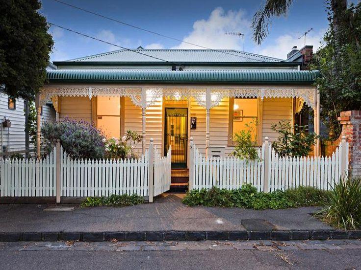 Corrugated iron edwardian house exterior with picket fence & decorative lighting