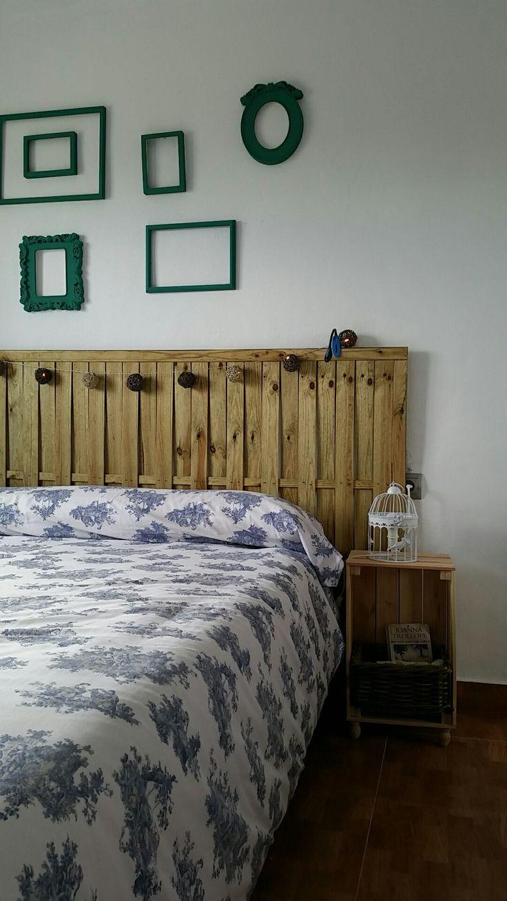 Dormitorio con cabecero de valla de madera y mesita de caja de frutas