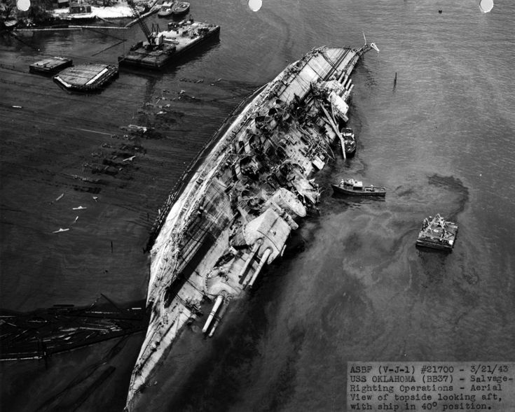 """Salvage operations, USS Oklahoma (BB-37), sunk during the Pearl Harbor attack. Aerial view of the battleship during righting operations, with the ship in the 40° position."""