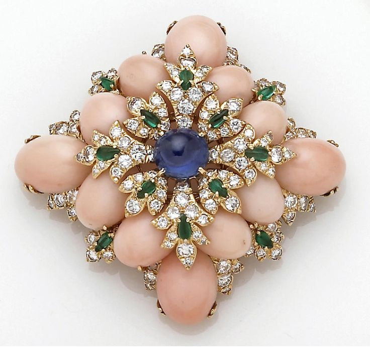 A coral and gem-set brooch, David Webb the lozenge-shaped panel centering an oval cabochon sapphire, diamond and emerald cluster within a surround of oval cabochon pink coral and further accented with an emerald and diamond border; sighed David Webb; estimated total diamond weight: 5.00 carats; mounted in eighteen karat gold
