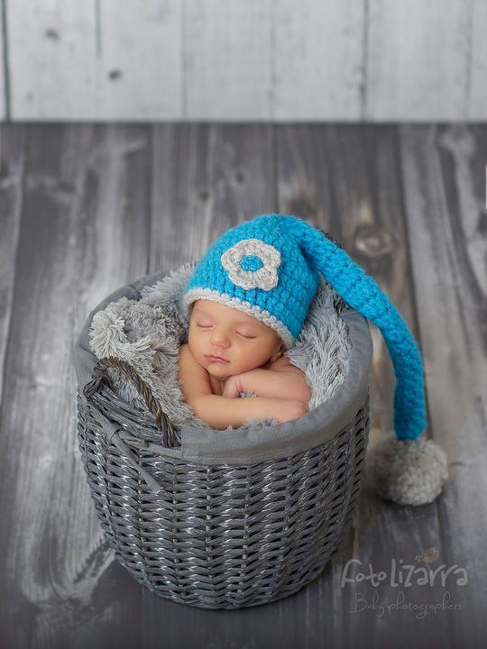 Fotografía de recién nacido de Irati dentro de una cesta con un gorro de lana azul y sobre fondo rústico. Newborn Photography.