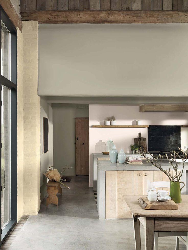 Beige kleur op de muur. Betonnen aanrechtblad en beton op de vloer. Houten keukendeurtjes.