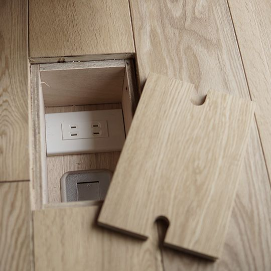 Outlet recessed with simple box, lid cut simply out of the floor board, and notched to give finger grips and pathway for cords to run.