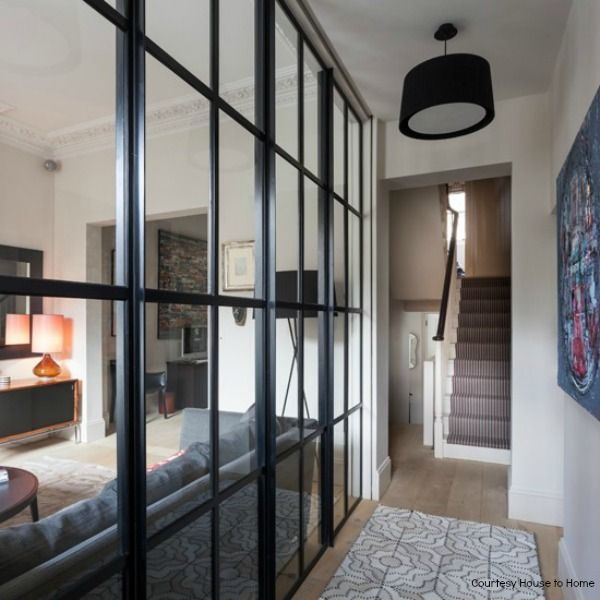 Open plan space with permanent glass panelled-Hallway from Homes andGardens via Housetohome. Loving the black lampshade and the black framed glass.