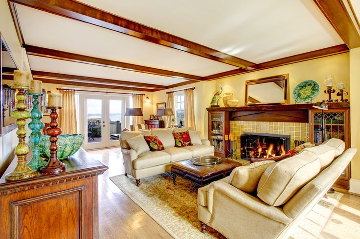 Living room features dark exposed beams and light hardwood flooring, with large fireplace surround comprised of tile and wood cabinetry. Twin cream couches sit across large leather ottoman.