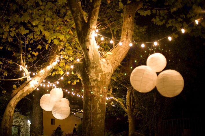 Hang in je tuin slingers van lampjes met lampionnen er aan.