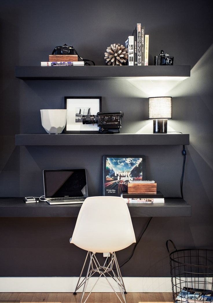 Dark wall with dark shelves and desk